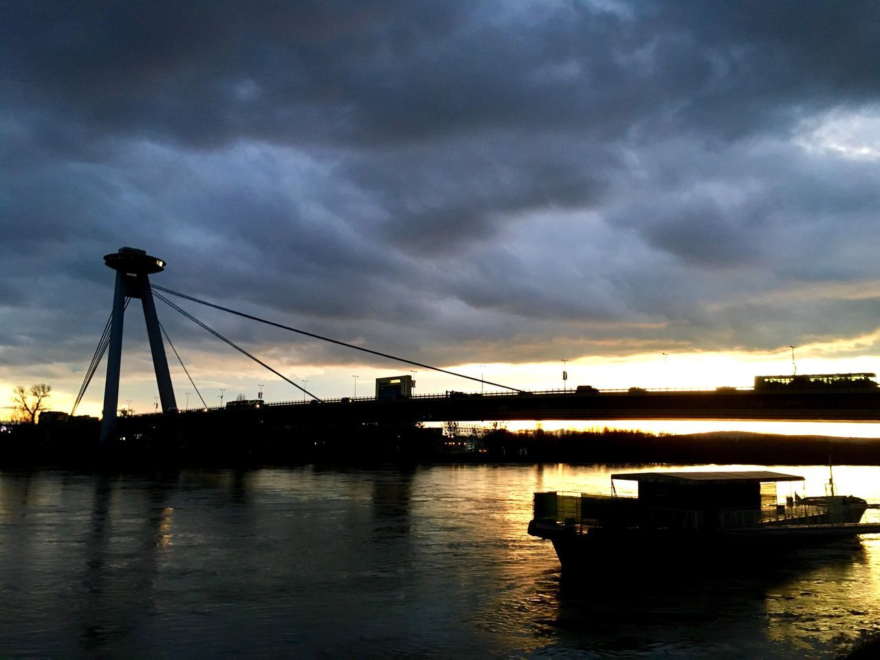 transportation, cloud - sky, connection, sky, bridge - man made structure, water, mode of transport, suspension bridge, sunset, nautical vessel, built structure, architecture, dramatic sky, outdoors, weather, waterfront, travel destinations, river, no people, travel, silhouette, scenics, nature, beauty in nature, city, day