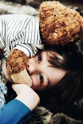 Close-up portrait of cute girl with teddy bear lying on bed at home