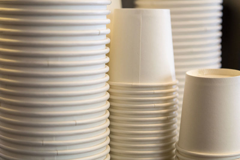 Close-up of stacked white disposable cups on table
