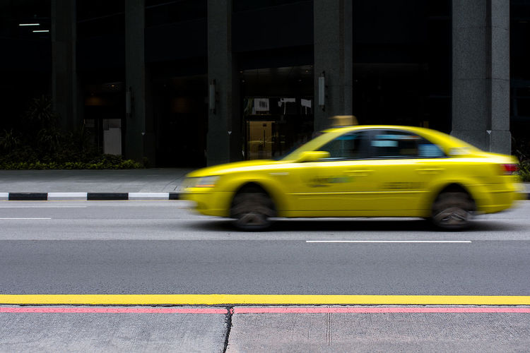 Yellow taxi of Singapore drives past in a motion blur on empty city road. Singapore Business District City City Life Curb Direction Driving Empty Empty Road Lines Motion Motion Blur Painted Lines Pavement RED LINE Road Road Markings Shadows Sidewalk Singapore Taxi Taxi Yellow Cab Yellow Line Yellow Taxi Transportation Mode Of Transportation Car Yellow Motor Vehicle Architecture Street Land Vehicle Road Marking Speed Blurred Motion Marking on the move Symbol Sign Built Structure No People Outdoors