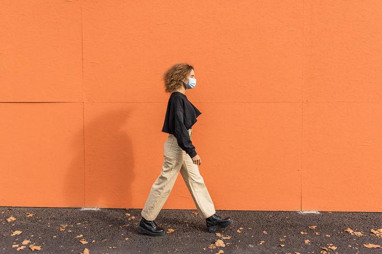 Full length of woman standing against orange wall
