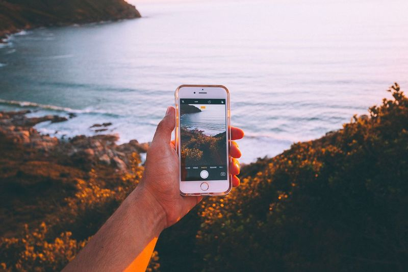 Man using smart phone at sunset