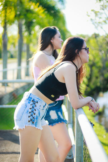 Side View Of Young Woman With Friend Standing By Railing