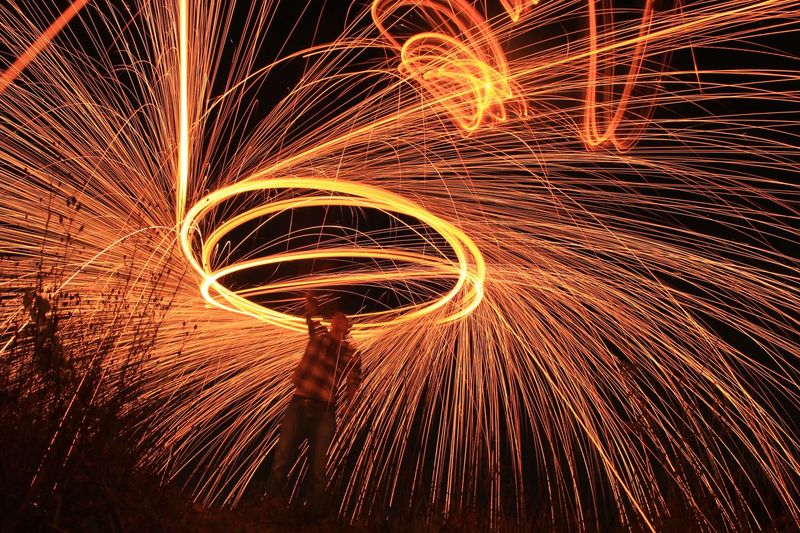 Man Standing Amidst Wire Wool On Field At Night