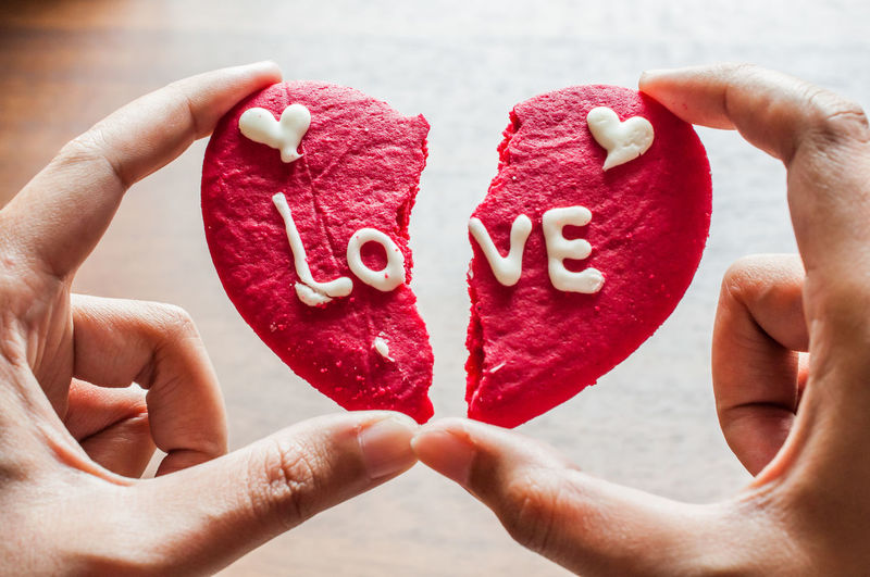 Cropped image of person holding broken heart shape cookie with text