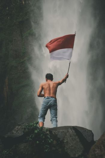Rear view of man standing on rock with indonesian national flag