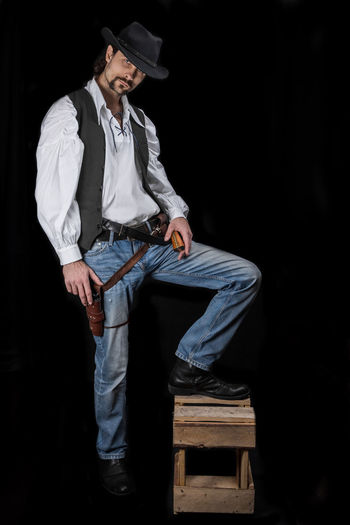 Handsome young man. This is an American cowboy. A vow to a white shirt, brown waistcoat and blue jeans. Black shoes on the feet. Carries a shtyapa, on a belt two pistols. The hair is of medium length; on the face is a beard and mustache. Authentic photo. Culture of America. Cowboy Wild West America American Gun National Authentic Moments Lifestyles Lifestyle One Person Candid Authentic Full Length Hat Young Adult Front View Young Men Clothing Men Black Background Males  Three Quarter Length Real People Fashion Contemplation