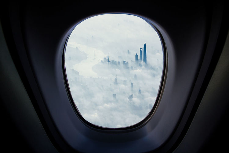 Modern buildings covered with clouds seen through airplane window