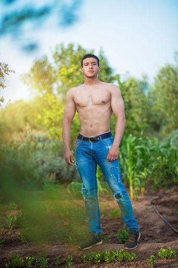 Full length portrait of shirtless man standing on land