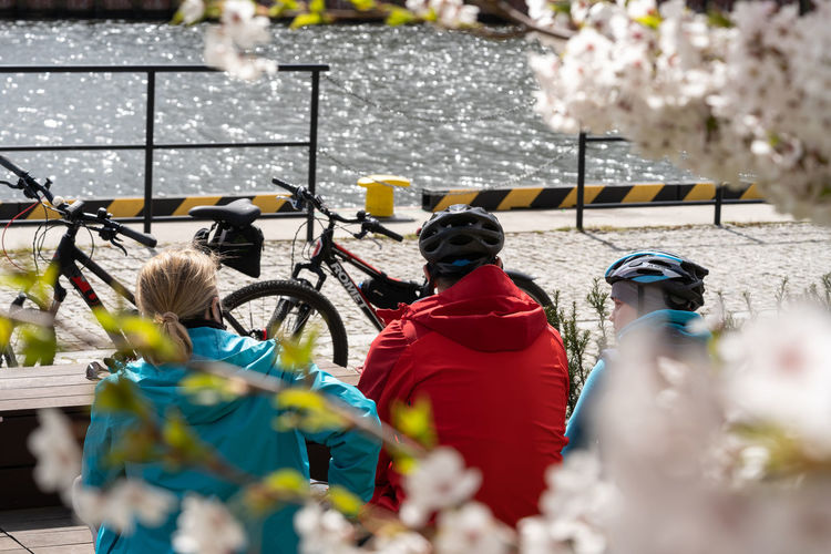 Rear view of people standing by bicycle during winter