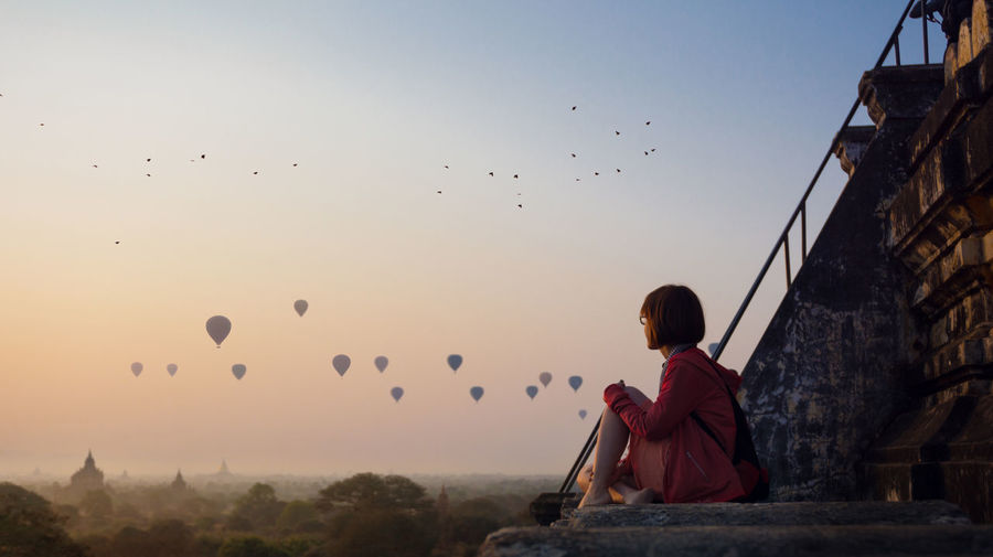 Side view of woman looking at hot air balloons flying against clear sky during sunset