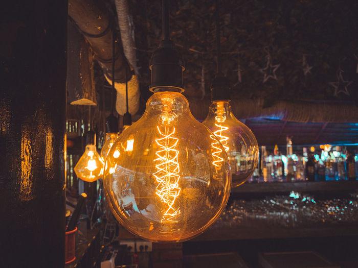 Illuminated light bulbs hanging at night