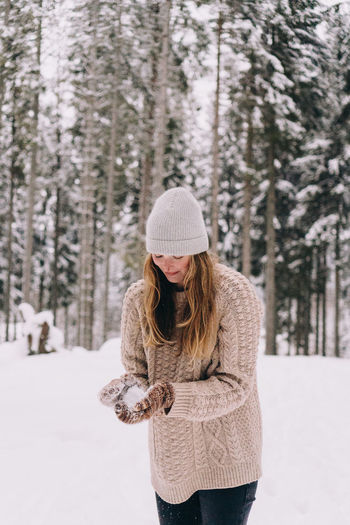 Woman wearing hat standing on snow covered land