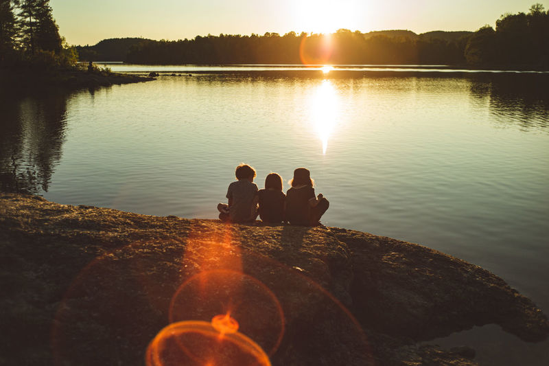 Children sitting by lake against sky during sunset