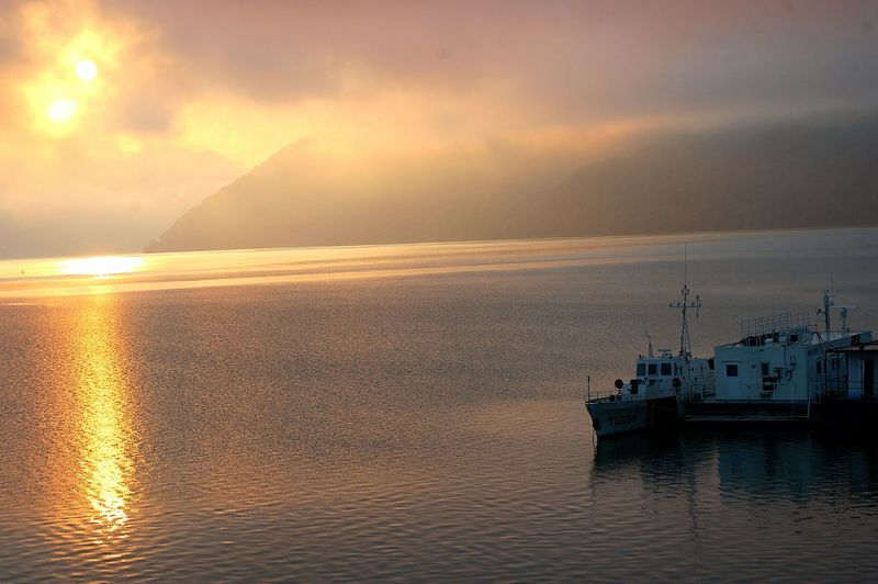 High angle view of trawlers sailing on river at sunset