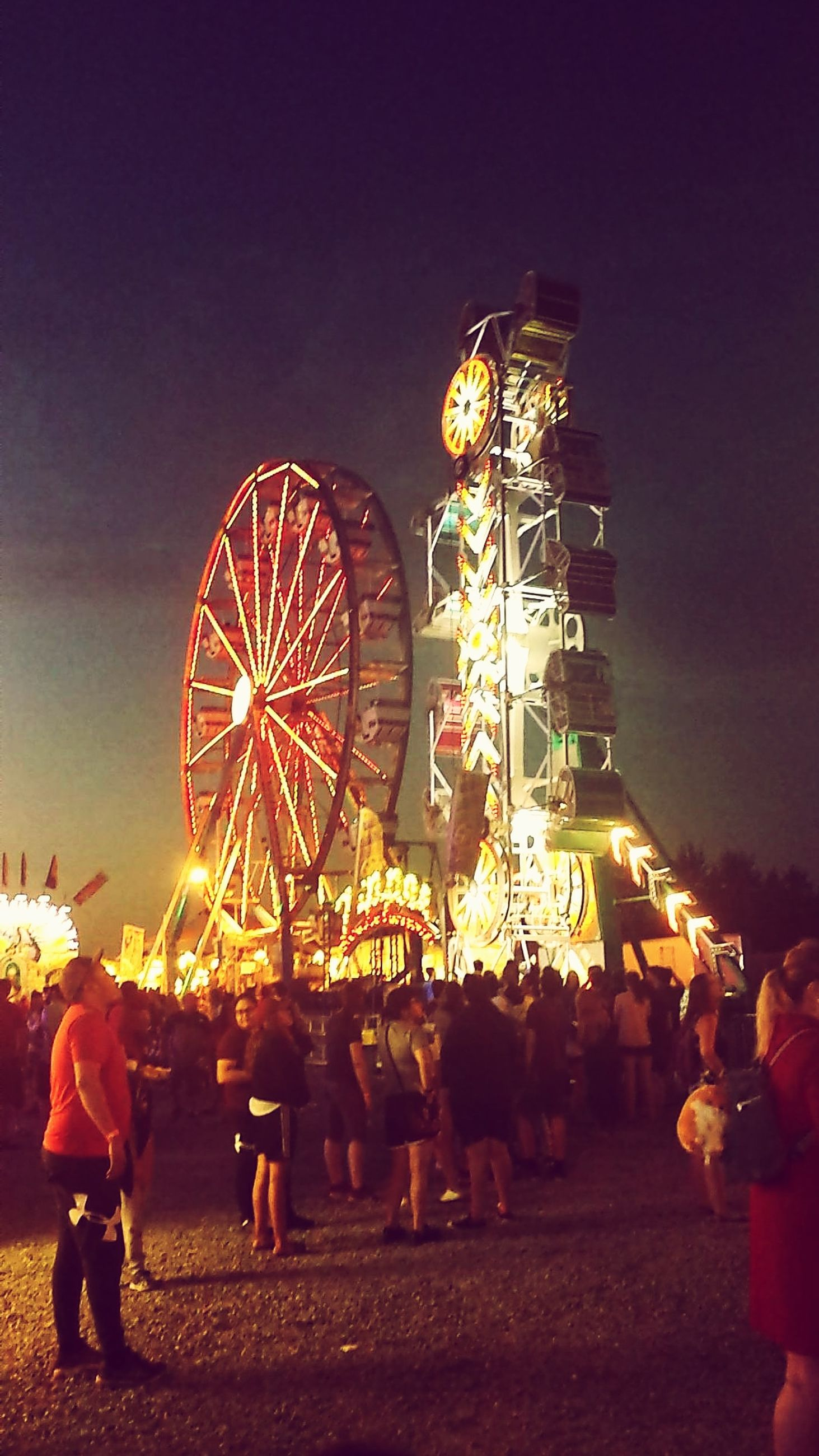 amusement park, amusement park ride, arts culture and entertainment, illuminated, group of people, ferris wheel, large group of people, night, real people, sky, crowd, leisure activity, enjoyment, motion, nature, women, outdoors, carnival, spinning, fairground, christmas market