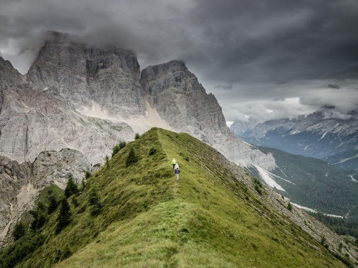 Mid distance image of people hiking on dolomites