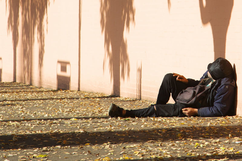 Side view of man sitting on floor in city