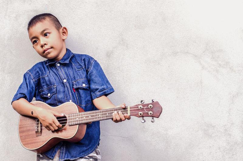 Boy playing guitar against wall