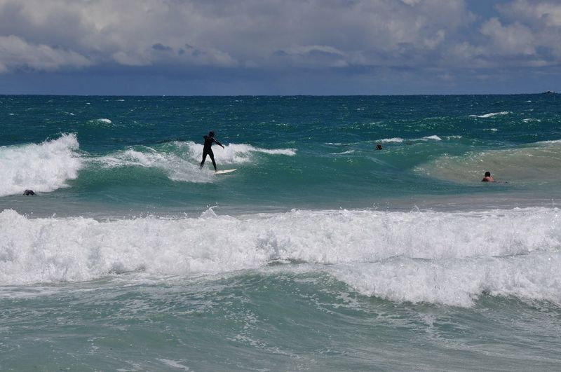 Surfers in the turquoise indian ocean waves at scarborough beach in western australia