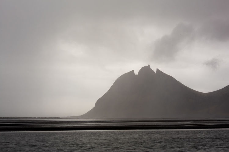 Silhouette mountain by sea against sky