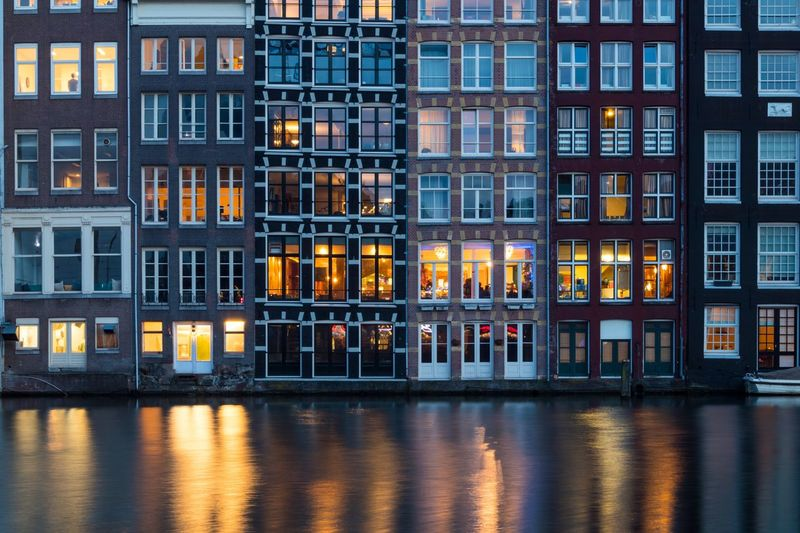 Damrak looking at buildings of Warmoesstraat Nederland Netherlands Holland Amsterdamse Grachten Amsterdam Canal Architecture Building Exterior Reflection Window Built Structure Night Outdoors Residential Building Waterfront City Water Travel Destinations