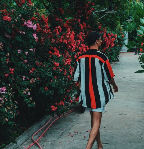 Full length of young woman standing against plants