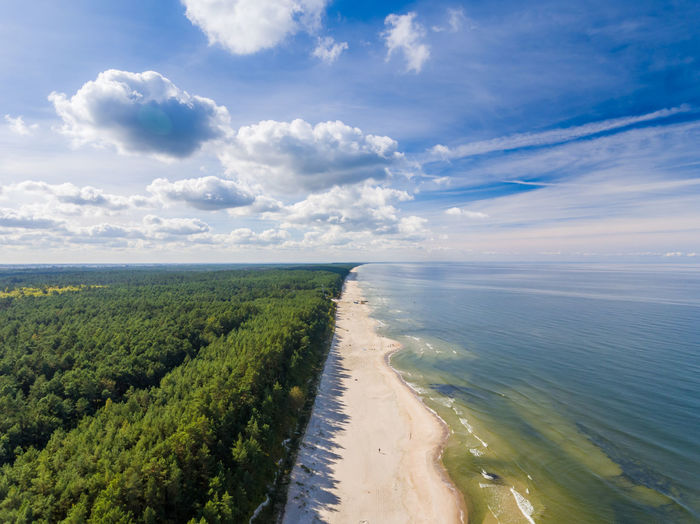 Puffy clouds on a deep blue sky over a sandy beach breaking between sea and forest Aerial View Beach Clouds Coast Drone  Flying High Forest Sea Sky