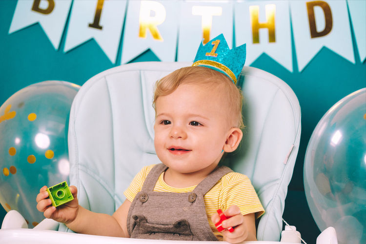Close-up of cute baby boy sitting on high chair in birthday party