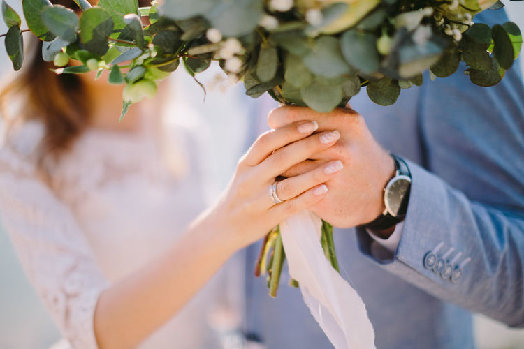 Midsection Of Bride And Groom Holding Bouquet