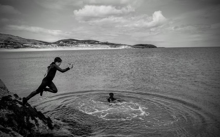 Side view of boy jumping in sea against cloudy sky