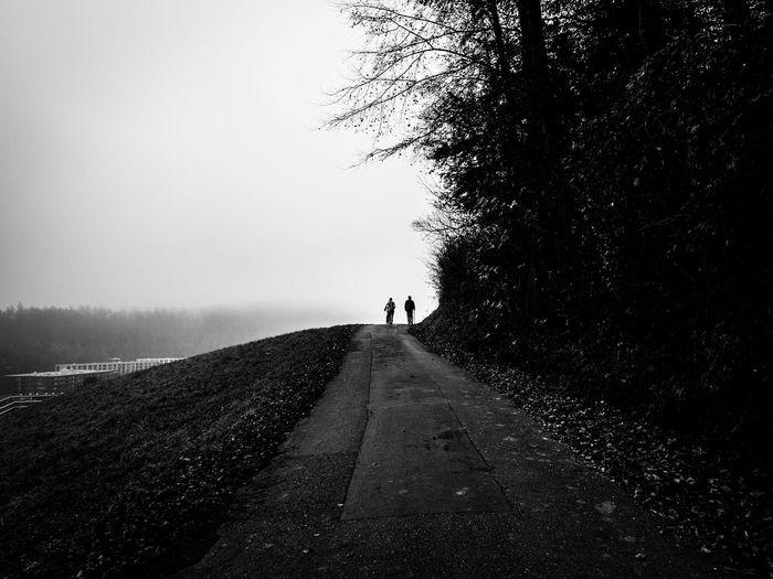 People Walking On Road Against Sky At Dusk