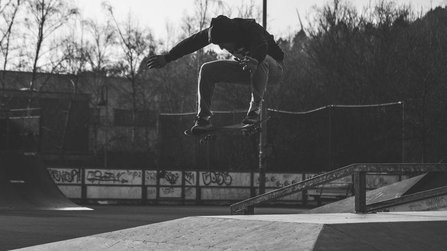 Man Skateboarding Against Trees In Park