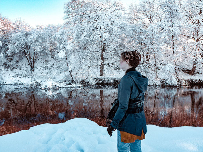 Woman standing by lake on snow covered land during winter