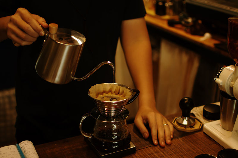 Midsection of man pouring coffee in kitchen