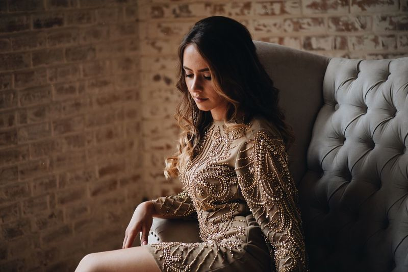 young beautiful girl lies on the couch One Person Real People Women Lifestyles Leisure Activity Sitting Adult Wall - Building Feature Three Quarter Length Indoors  Young Women Beauty Young Adult Fashion Beautiful Woman Looking Pattern Furniture Sofa Contemplation