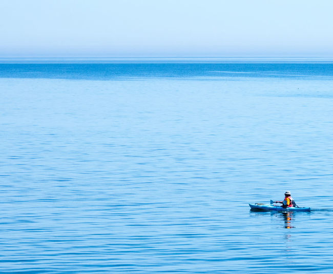 Person kayaking in sea against clear sky