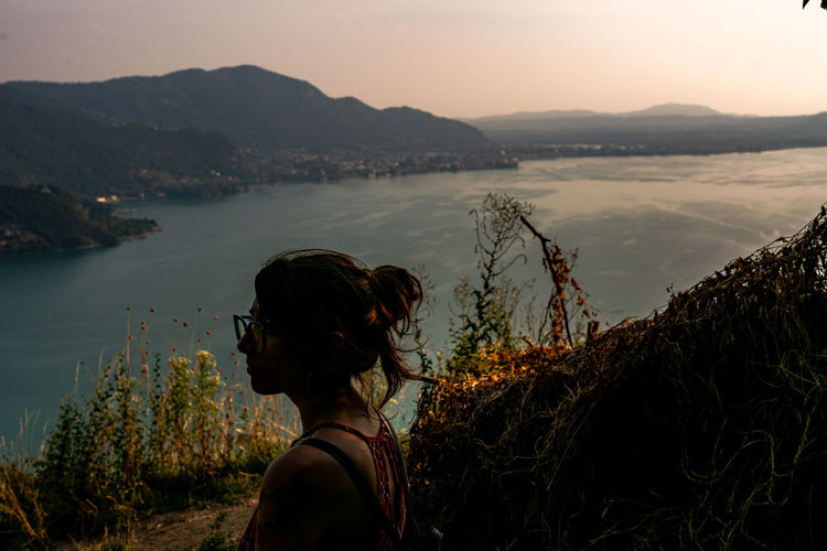 Side view of woman looking at sea while standing on mountain against sky