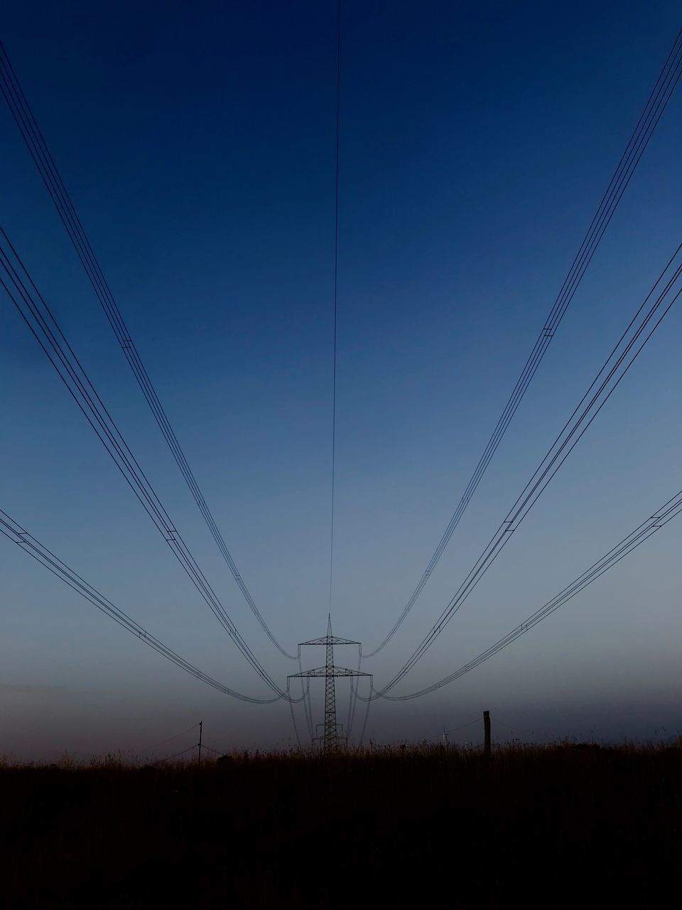 ELECTRICITY PYLONS ON FIELD AGAINST CLEAR SKY