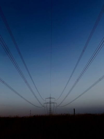 Electricity pylons on field against clear blue sky