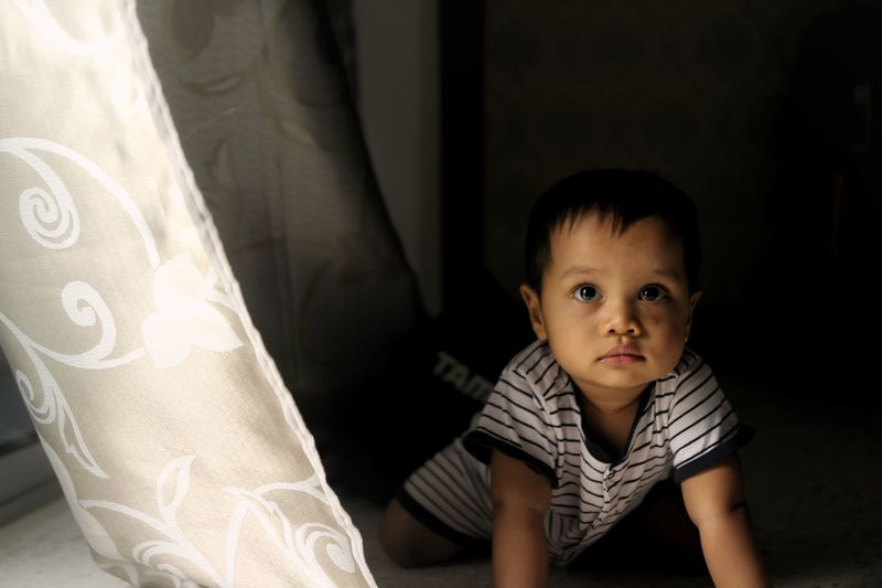 Cute baby boy crawling by curtain at home