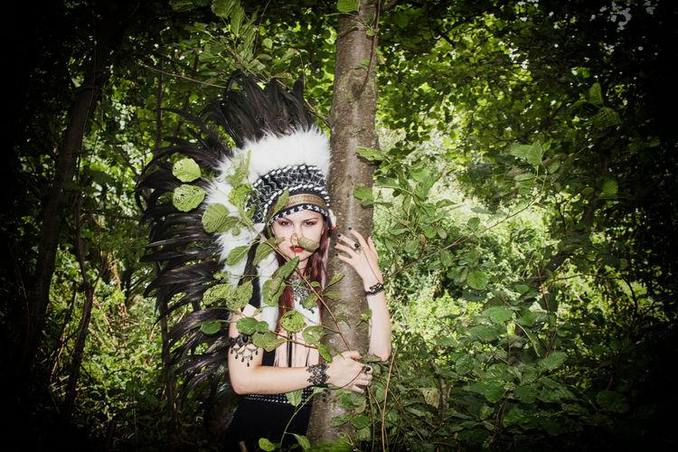 Portrait of woman wearing headdress in forest
