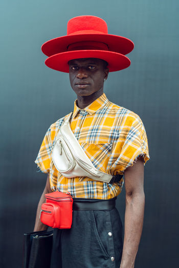 Portrait of man holding hat standing against wall