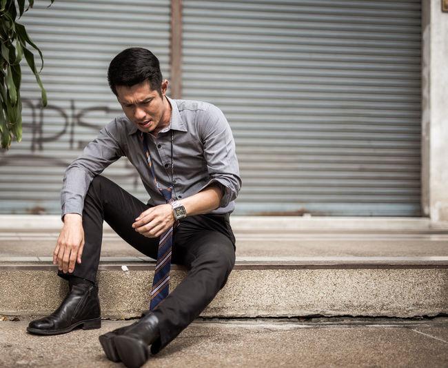 Businessman Sitting On Footpath