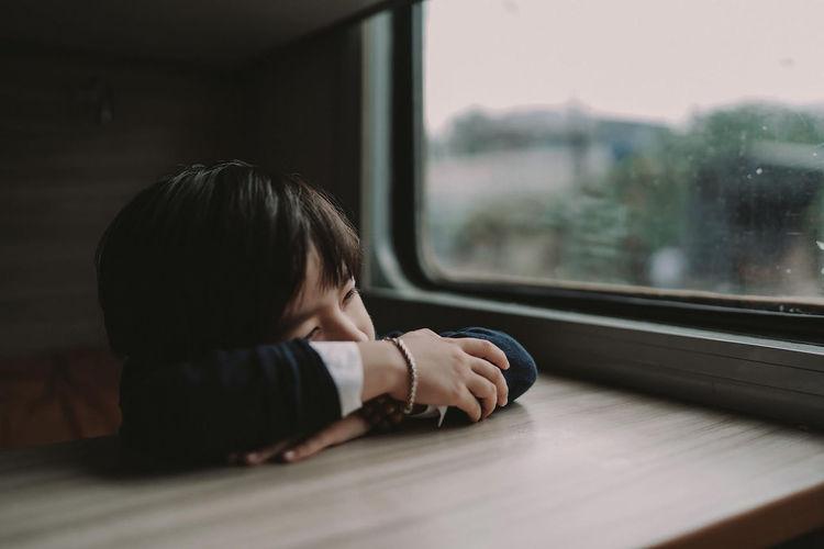 Boy relaxing on table by window in train