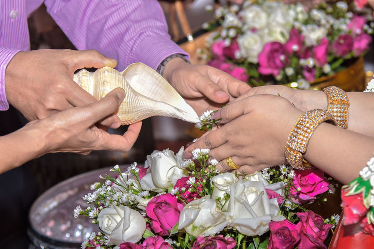 Cropped Image Of Man And Woman Holding Seashell Over Bride Hands During Wedding Ceremony