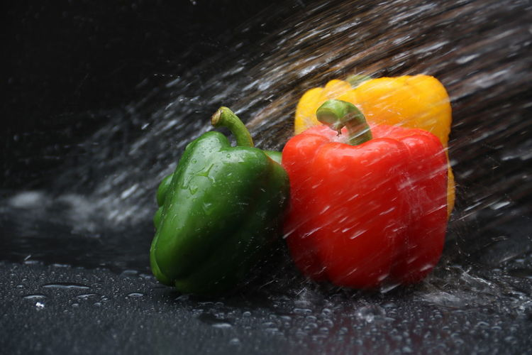 Close-up of wet red bell peppers on black background