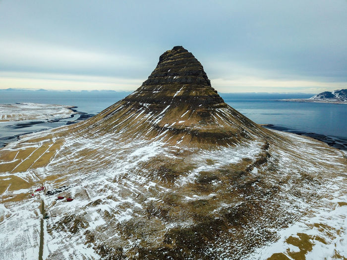 Kirkjufell Aerial Shot Kirkjufell Aerial Aerial View Beach Beauty In Nature Cloud - Sky Cold Temperature Day Idyllic Land Mountain Nature No People Non-urban Scene Outdoors Scenics - Nature Sea Sky Snow Snowcapped Mountain Tranquil Scene Tranquility Water Winter