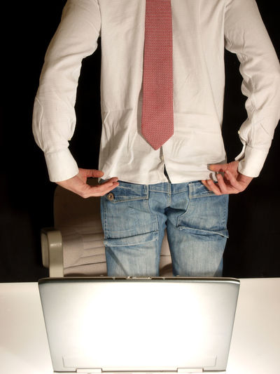 Man with tie on his back standing next to desk