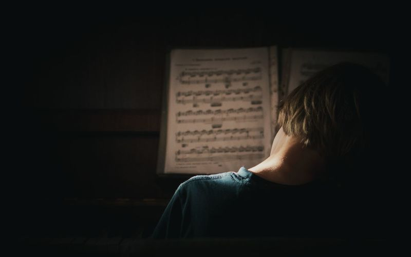 Rear view of boy playing piano while playing piano with music note at home